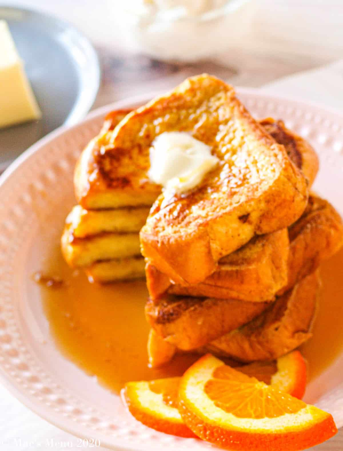 A side angle shot of a large stack of brioche french toast with a wedge cut out