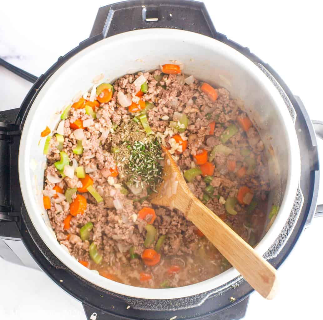 Ground meat, veggies, and herbs in a pressure cooker