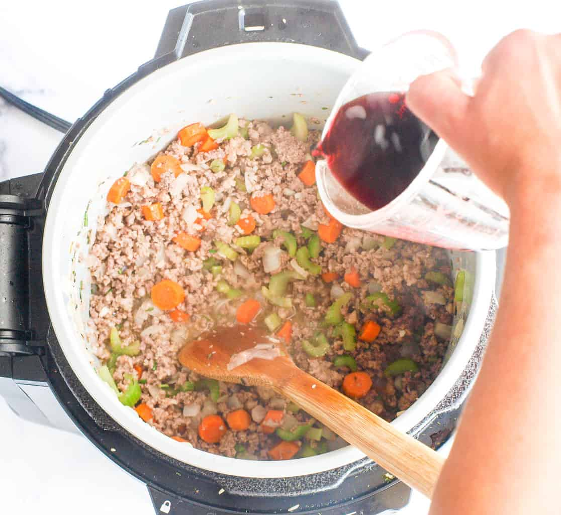 Pouring the wine into the ground meat and veggies in the pressure cooker