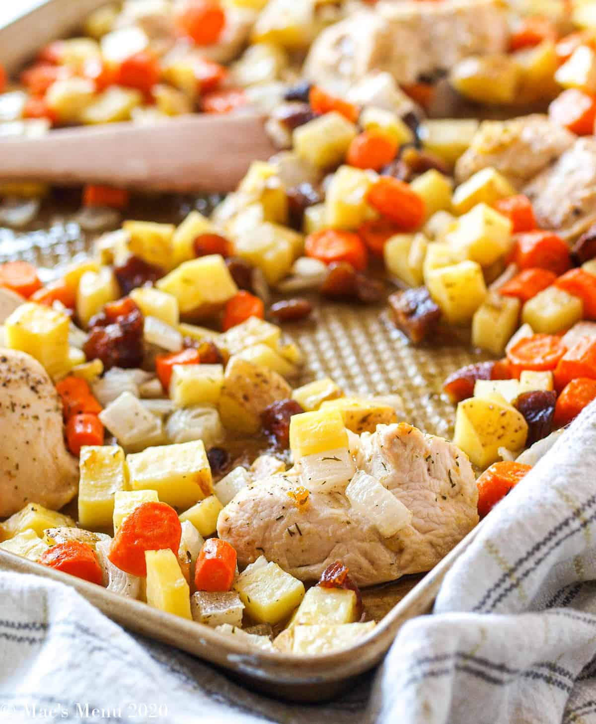 A large baking sheet full of the sheet pan apricot chicken and potatoes with a wooden spoon on the tray with the food