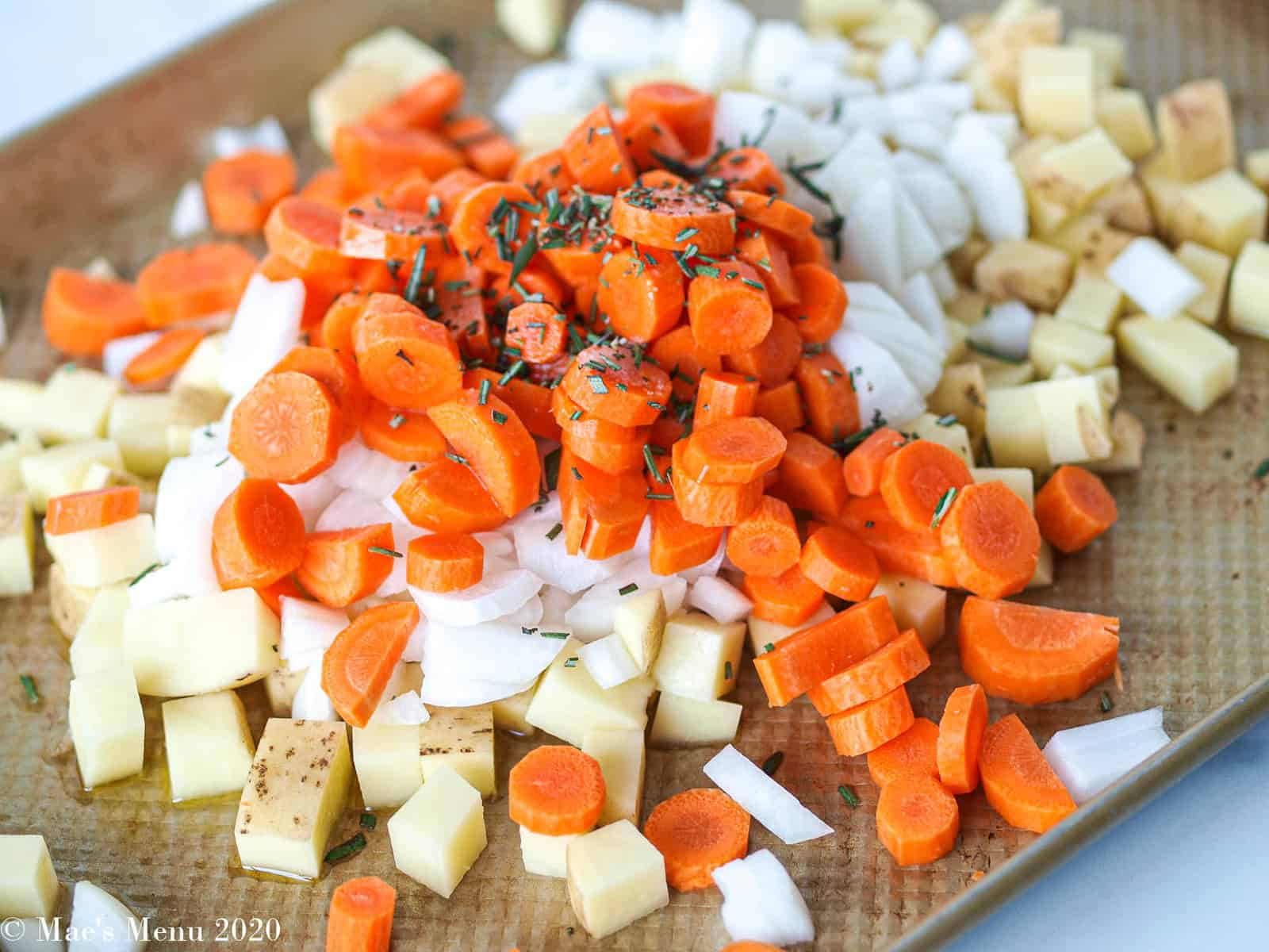 Potatoes, onions, and carrots with dried spices on a baking sheet