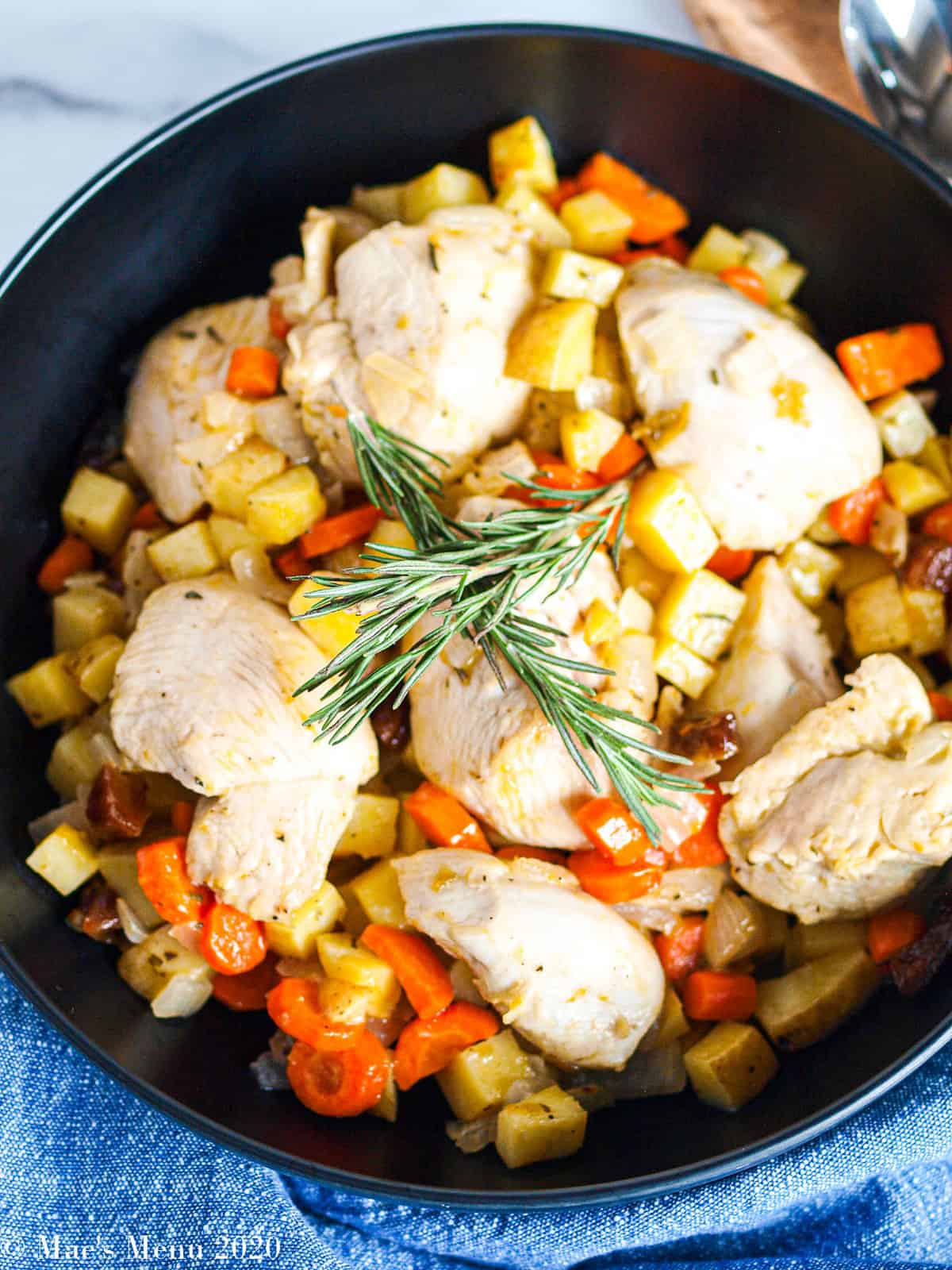 An overhead shot of a large black serving bowl with sheet pan apricot chicken and vegetables in it