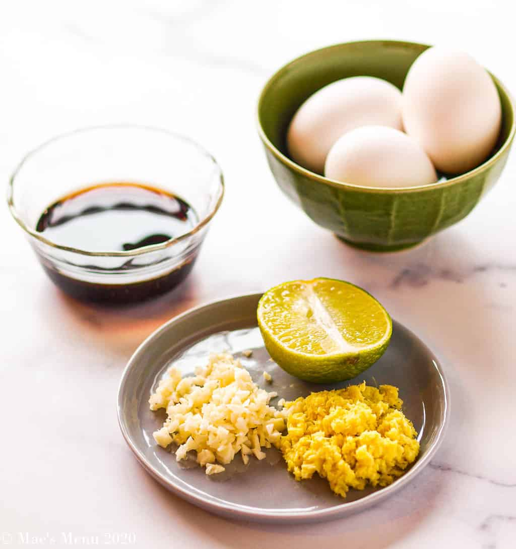 3 ingredients for house special fried rice: a dish of soy sauce, a plate of garlic, lime and ginger; and 3 eggs