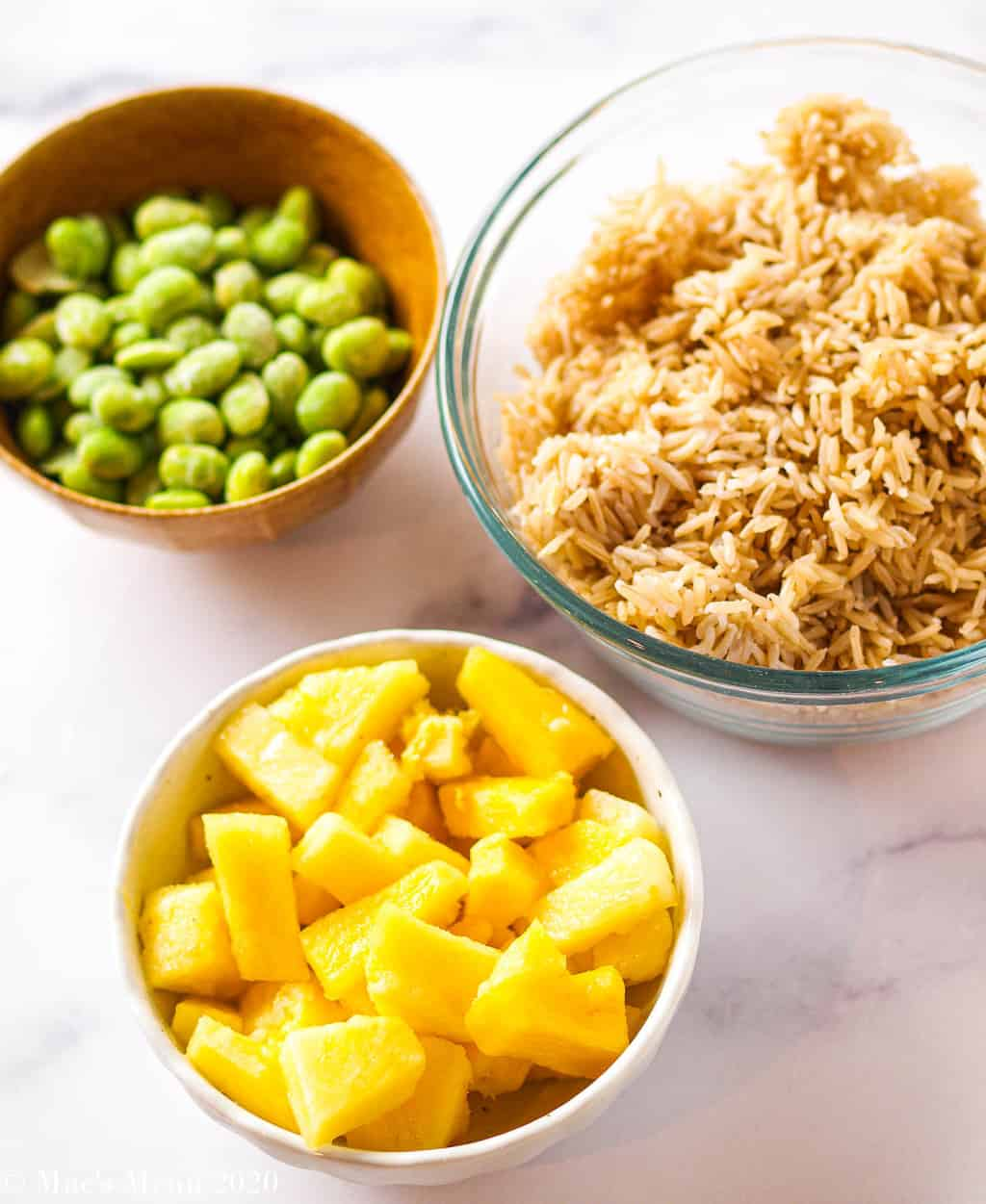 Three dishes of ingredients: brown rice, frozen pineapple, and shelled edamame