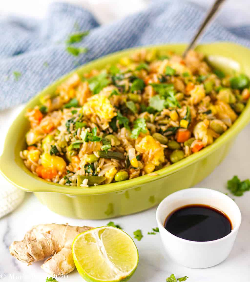 A large green dish of house special fried rice next to lime, ginger, and a dish of soy sauce