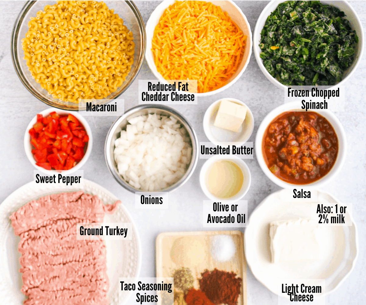 All the ingredients for taco macaroni and cheese -- macaroni, reduced-fat cheese, frozen chopped spinach, salsa, butter, olive or avocado oil, onions, sweet pepper, ground turkey, taco spice blend, light cream cheese, and milk