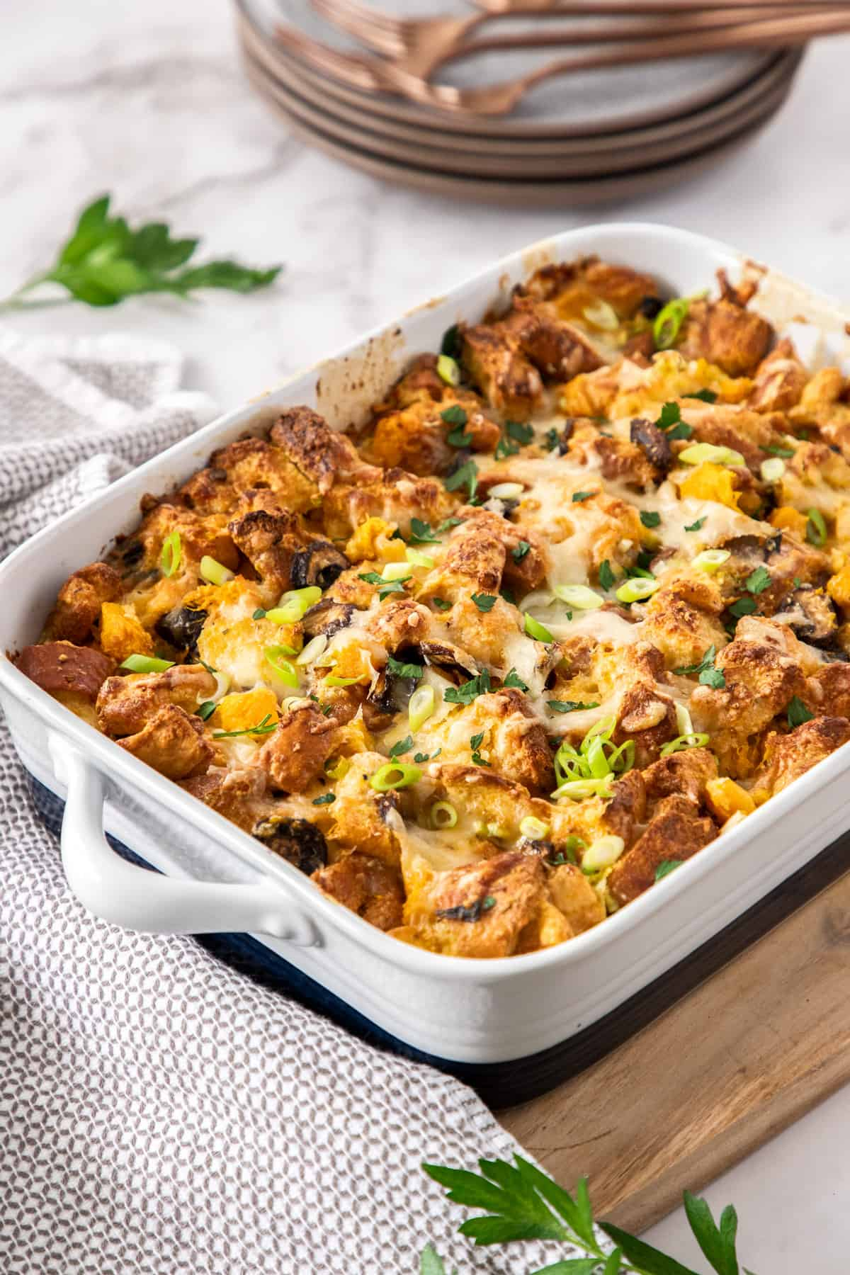 A white and blue baking dish full of savory bread pudding