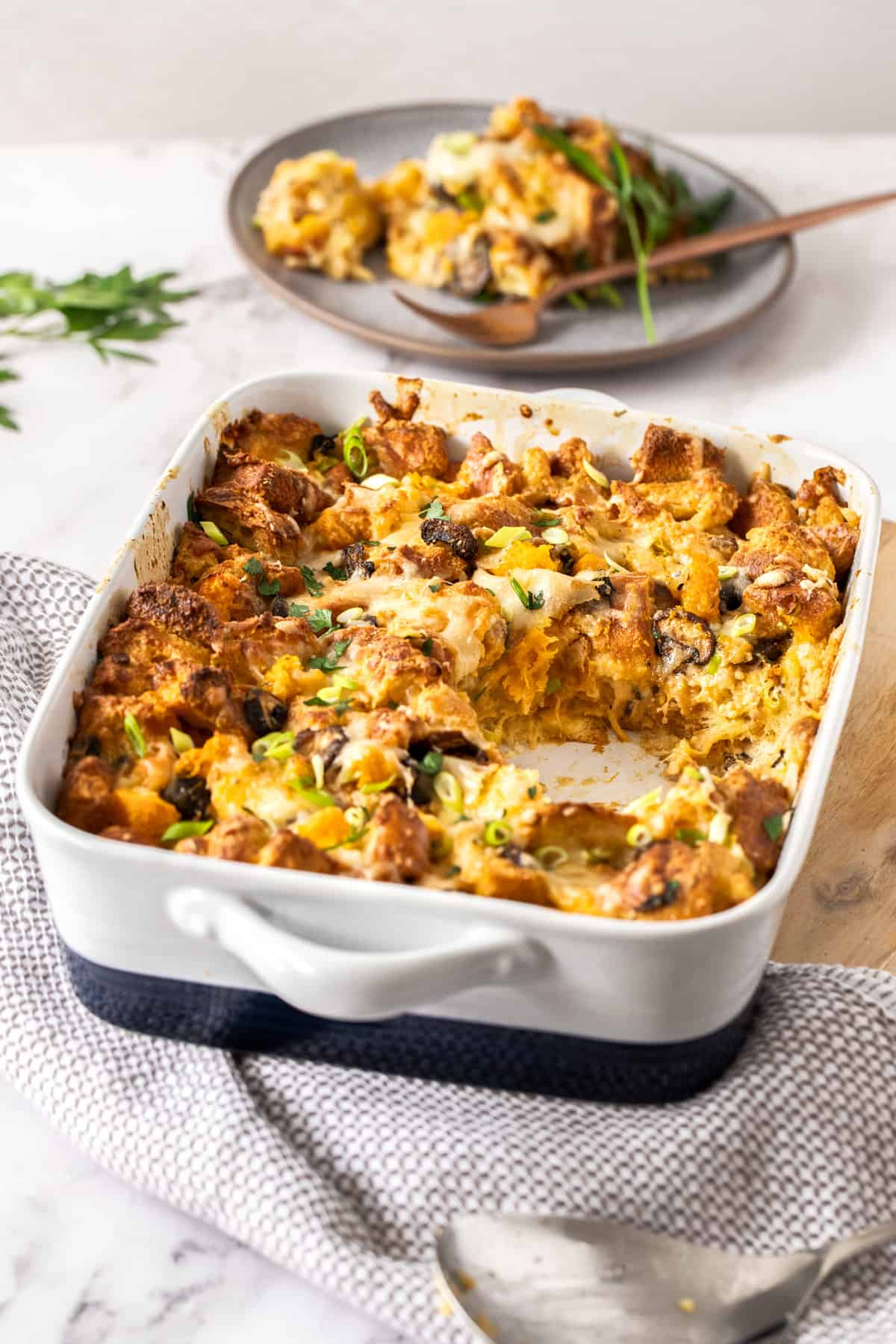 A large white dish of savory bread pudding with a scoop of the pudding on a plate behind the dish