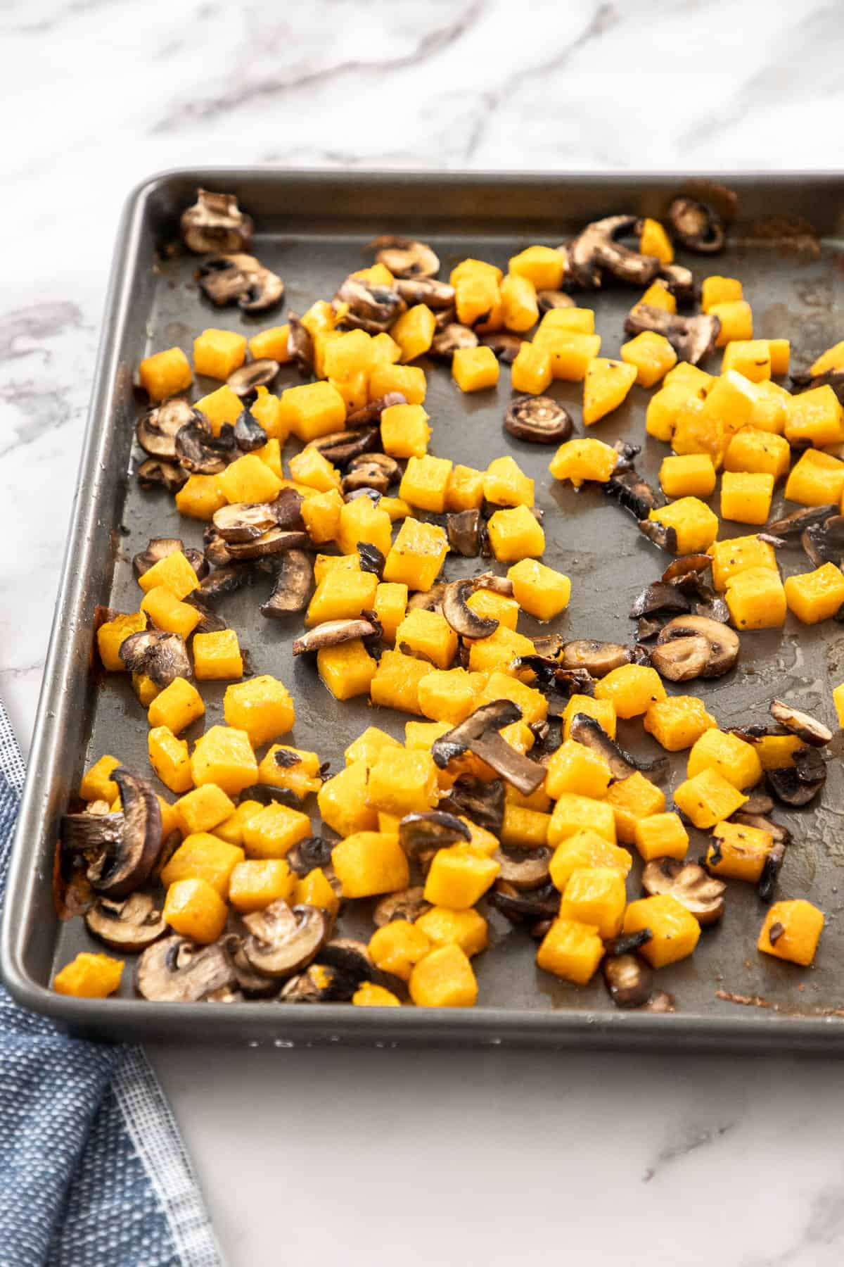 Roasted mushrooms and butternut squash on a baking sheet