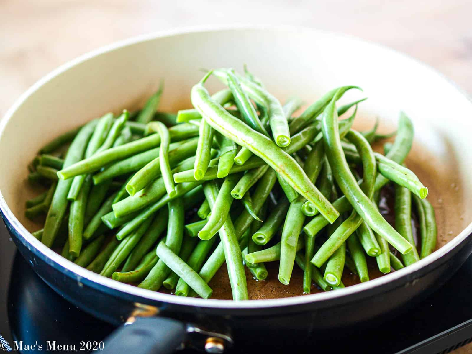 A side-angled shot of a large skillet full of green beans