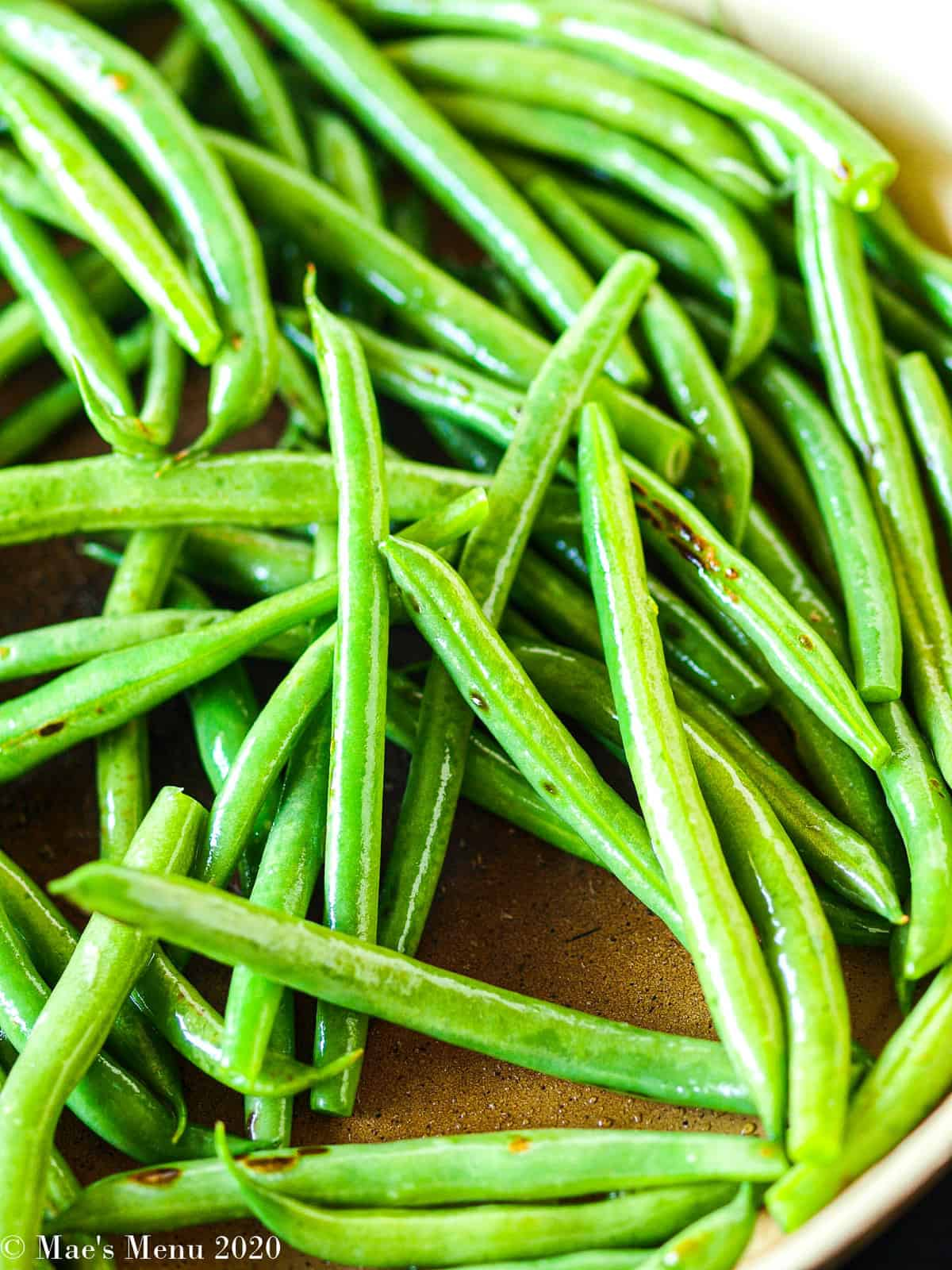 Green beans starting to cook in a large non-stick skillet