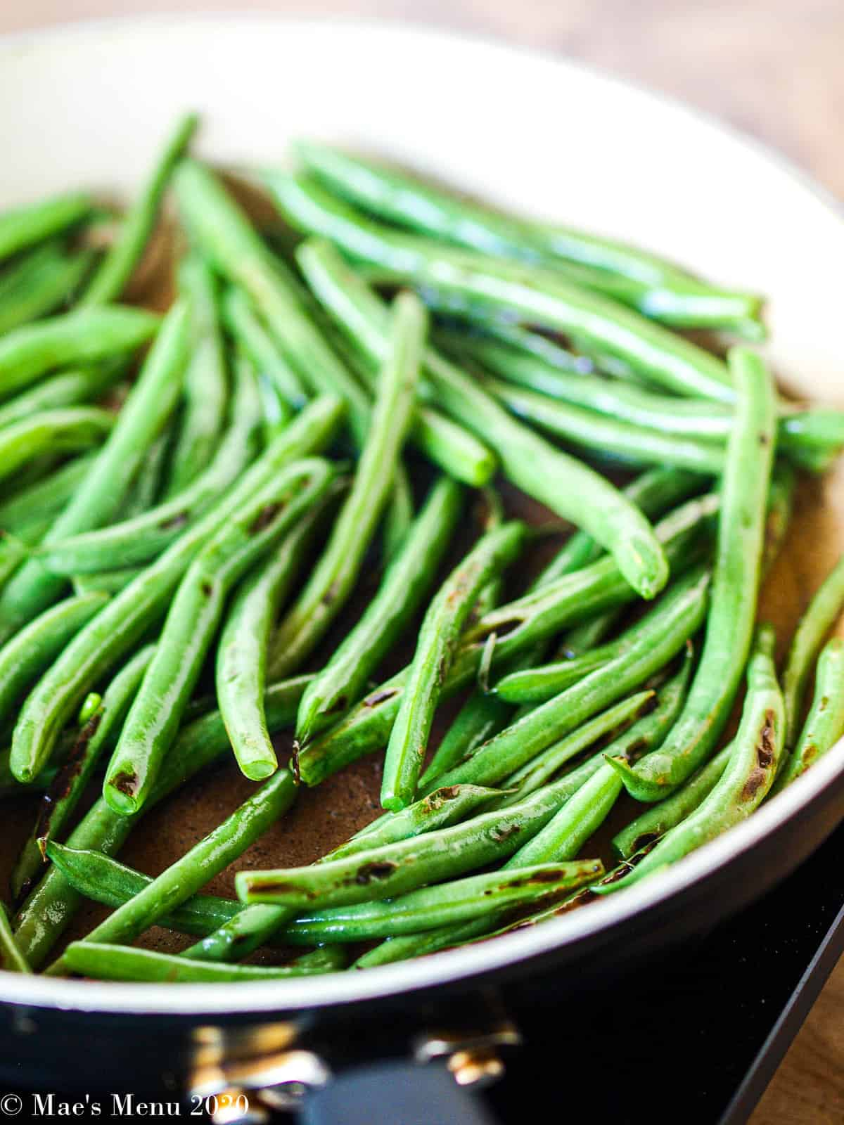 The green beans blistering up in a large non-stick pan