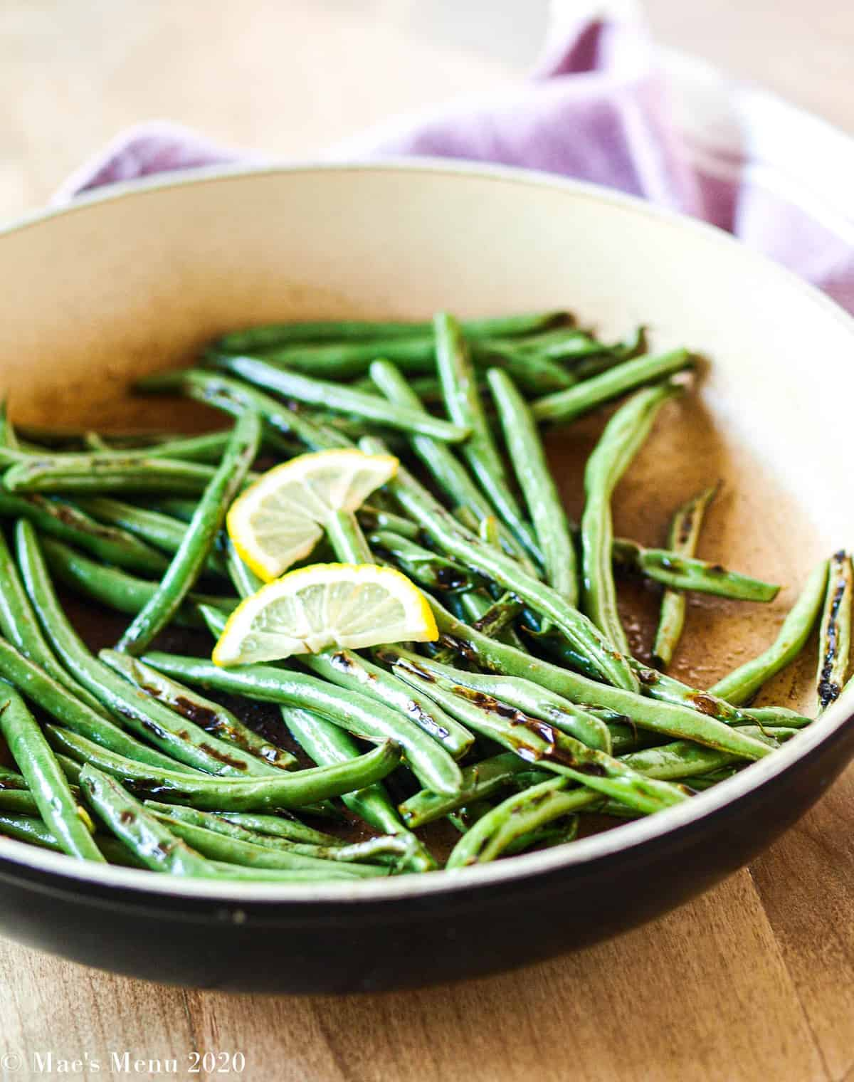 A large non-stick skillet full of blistered green beans