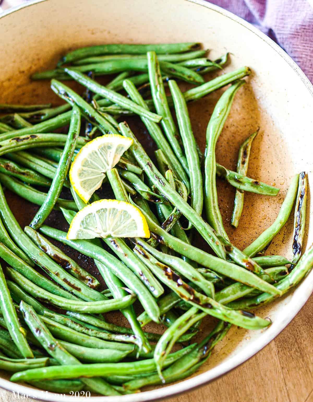 An overhead shot of a skillet full of blistered green beans
