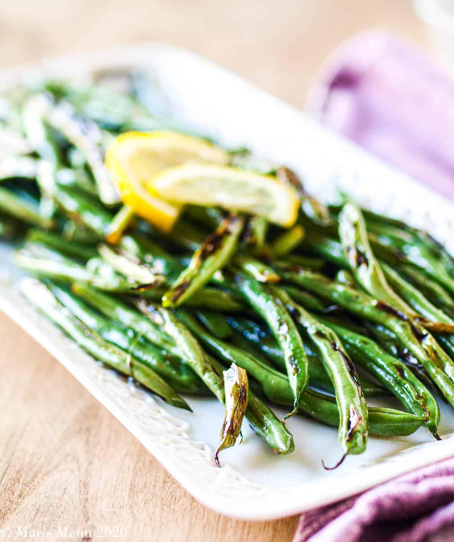 A side shot of a white platter of blistered green beans