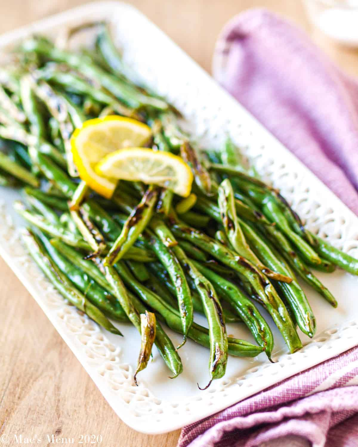 Side-angled shot of blistered green beans on a white tray
