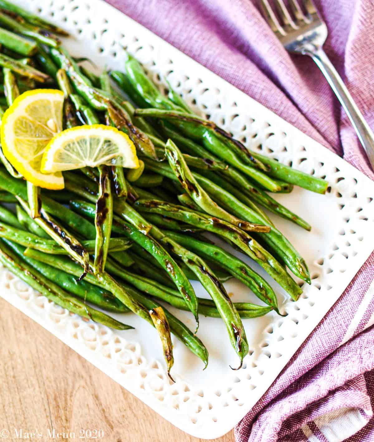 An overhead shot of a white platter full of blistered green beans