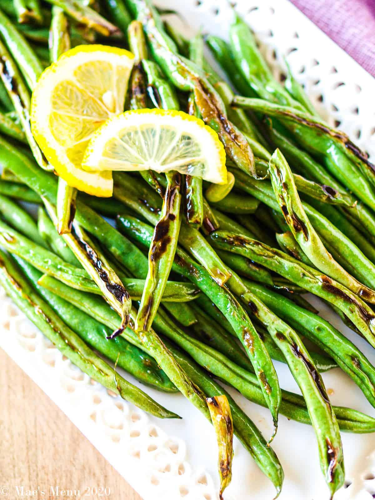 An overhead shot of a white platter of green beans