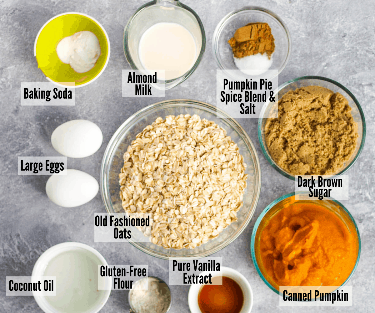 All the ingredients for gluten-free pumpkin muffins: baking soda, almond milk, pumpkin pie spice and salt, dark brown sugar, canned pumpkin, old fashioned oats, pure vanilla extract, gluten-free flour, coconut oil, and eggs
