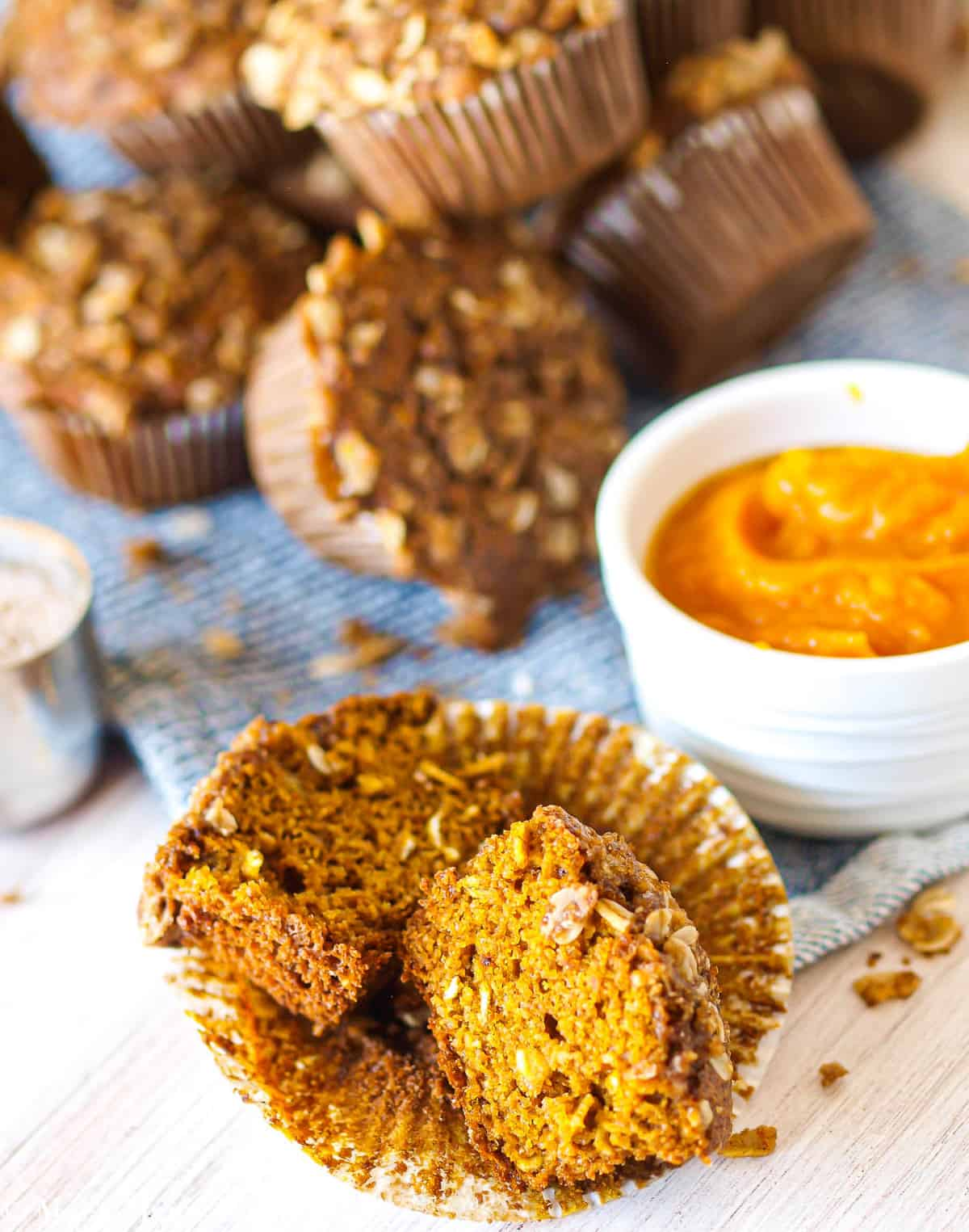 a gluten-free pumpkin muffin split in half in front of a pile of muffins