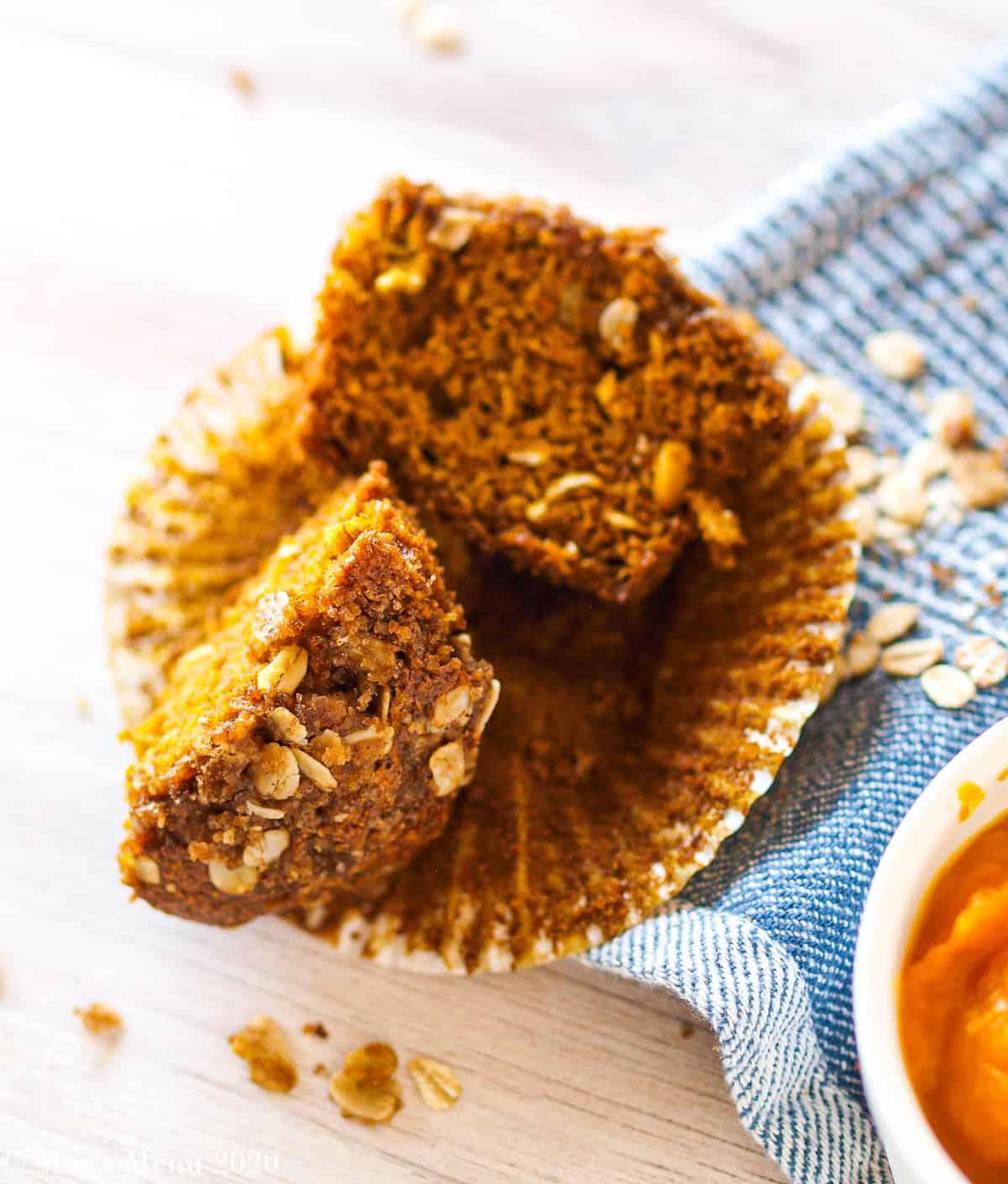 A split gluten-free pumpkin muffin next to a dish of pumpkin