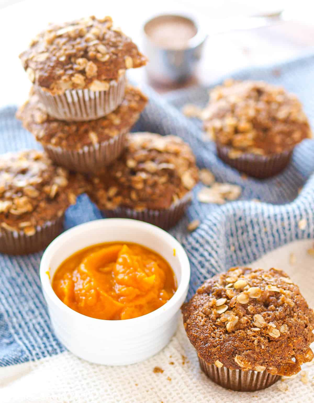 A stack of gluten-free pumpkin muffins with a muffin and dish of pumpkin in front