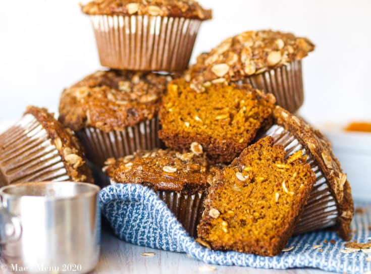A pale of gluten-free pumpkin muffins on a blue towel with a silver measuring cup in front of them