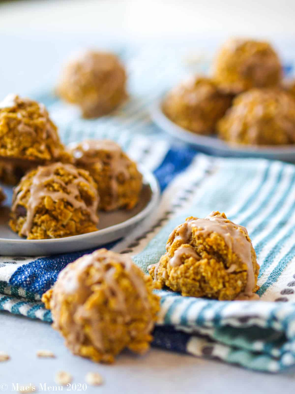 Oatmeal pumpkin cookies on a dish with 2 cookies on a towel in front of them