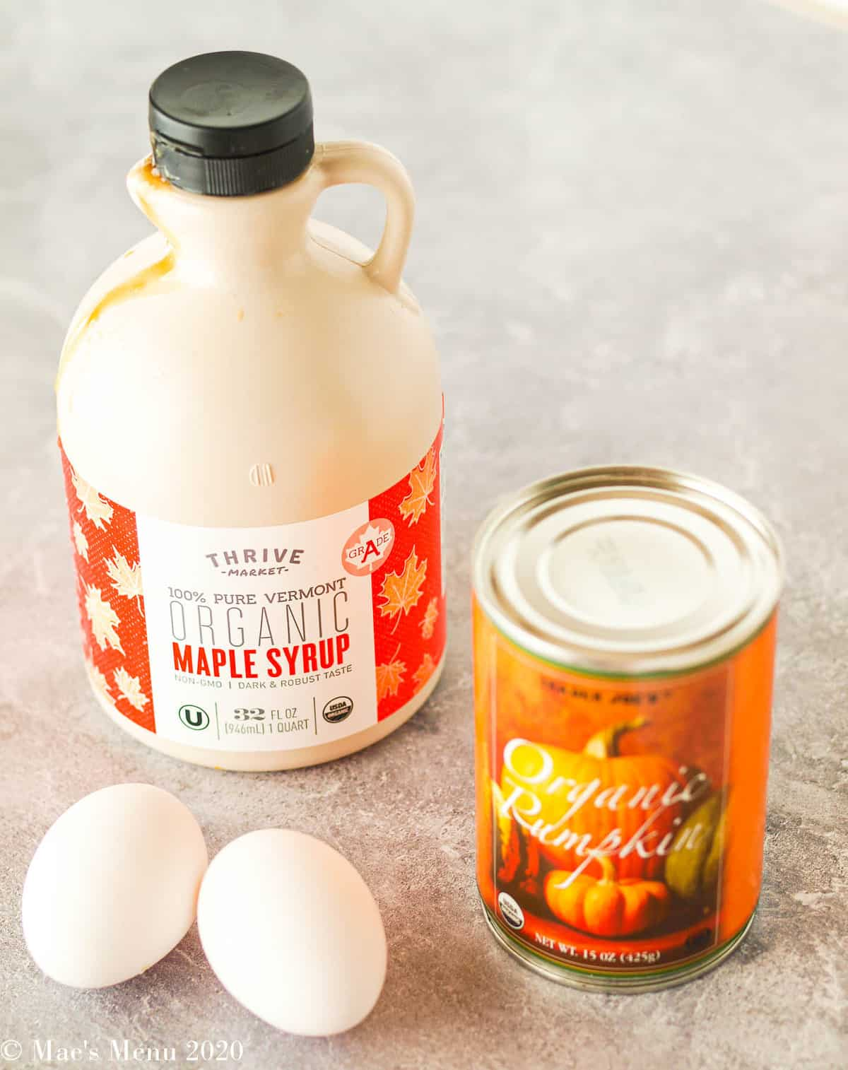 A jug of maple syrup, can of pumpkin, and 2 eggs