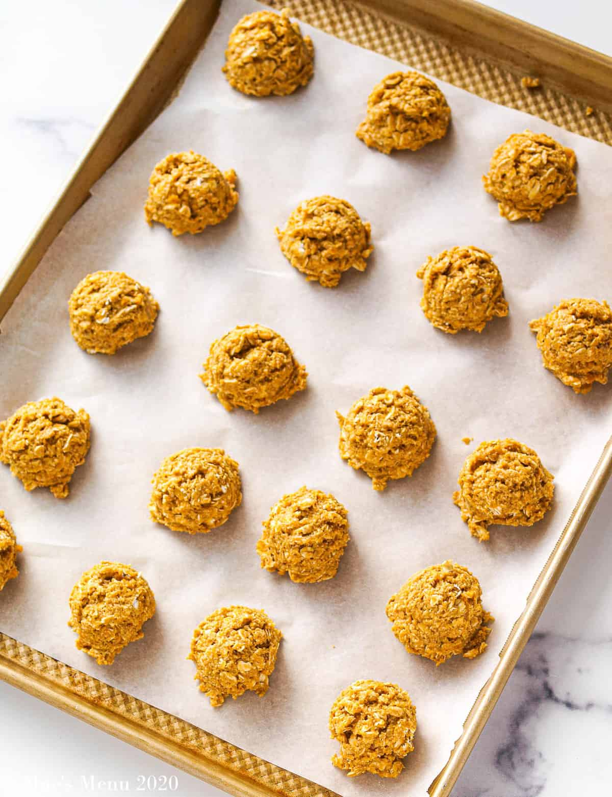 Balls of cookie batter on a cookie sheet lined with parchment paper