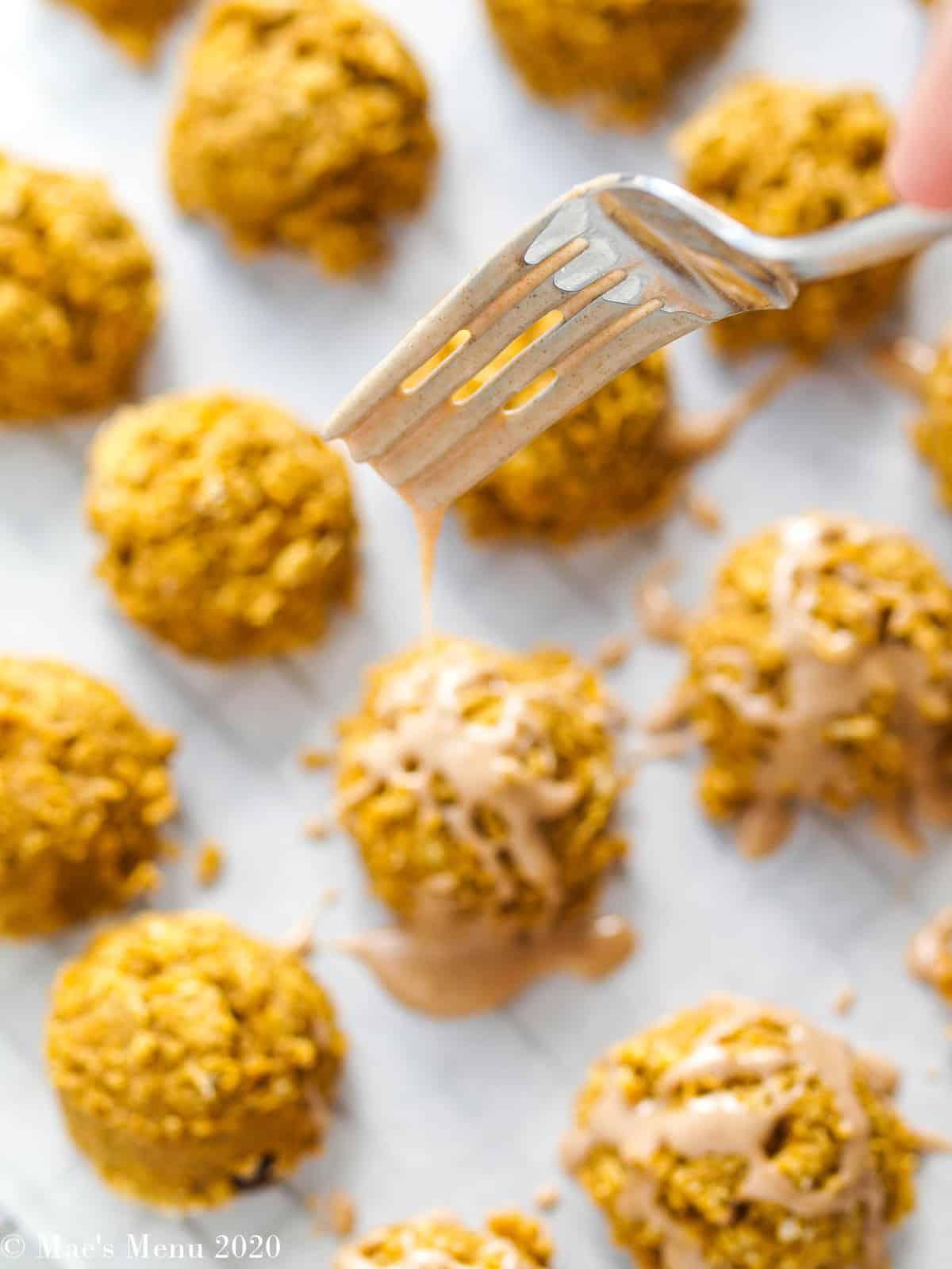 Drizzling the cinnamon maple glaze on the gluten-free oatmeal pumpkin cookies
