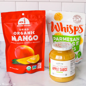Snacks from thrive market on the counter: a bag of mangoes, a bottle of applesauce, and a bag of parmesan cheese whisps