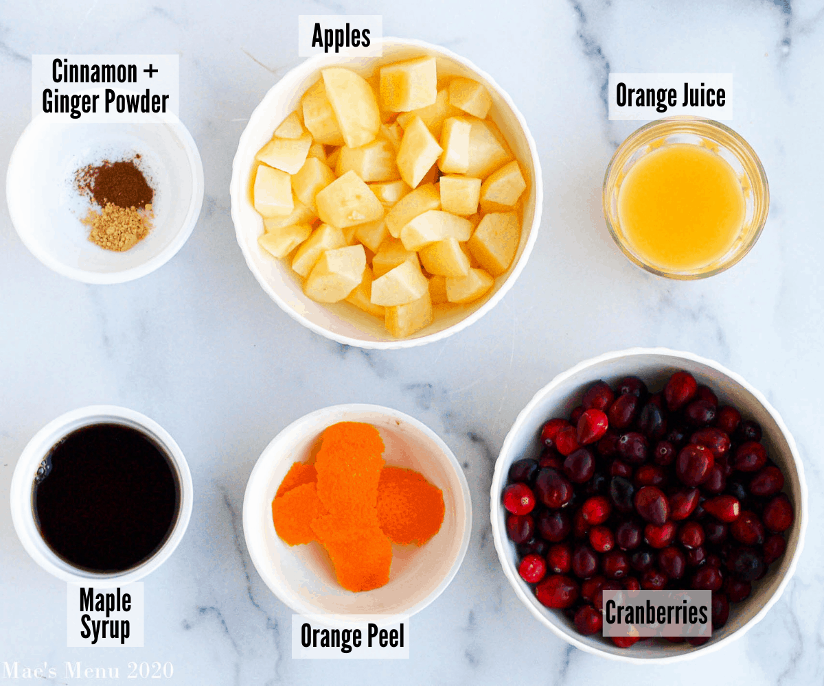 All of the ingredients for apple cranberry sauce: apples, orange peel, cranberries, orange juice, cinnamon and ginger powder, maple syrup
