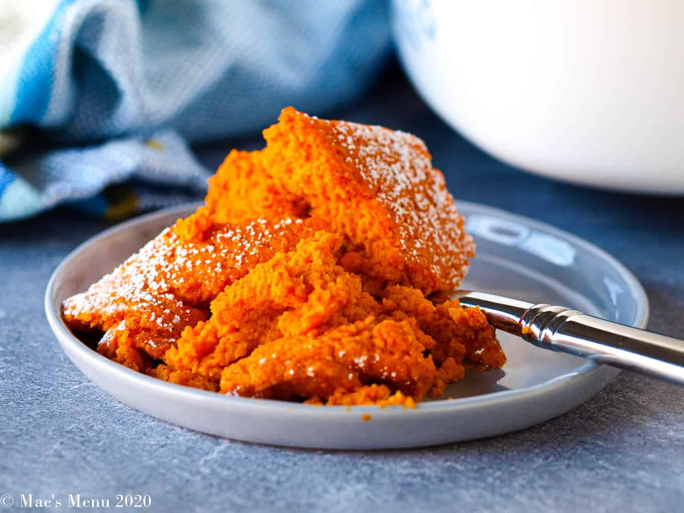 An up-close shot of a large scoop of carrot souffle on a smoky blue small plate