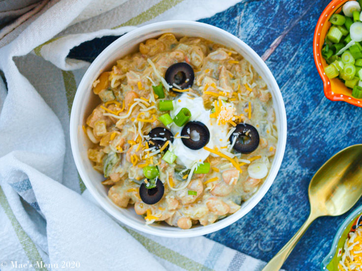 An up-close overhead shot of a bowl of white bean turkey chili on a blue wooden background