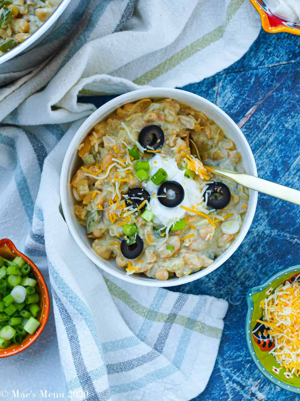 An overhead shot of a bowl of leftover white bean turkey chili surrounded by bowls of turkey toppings