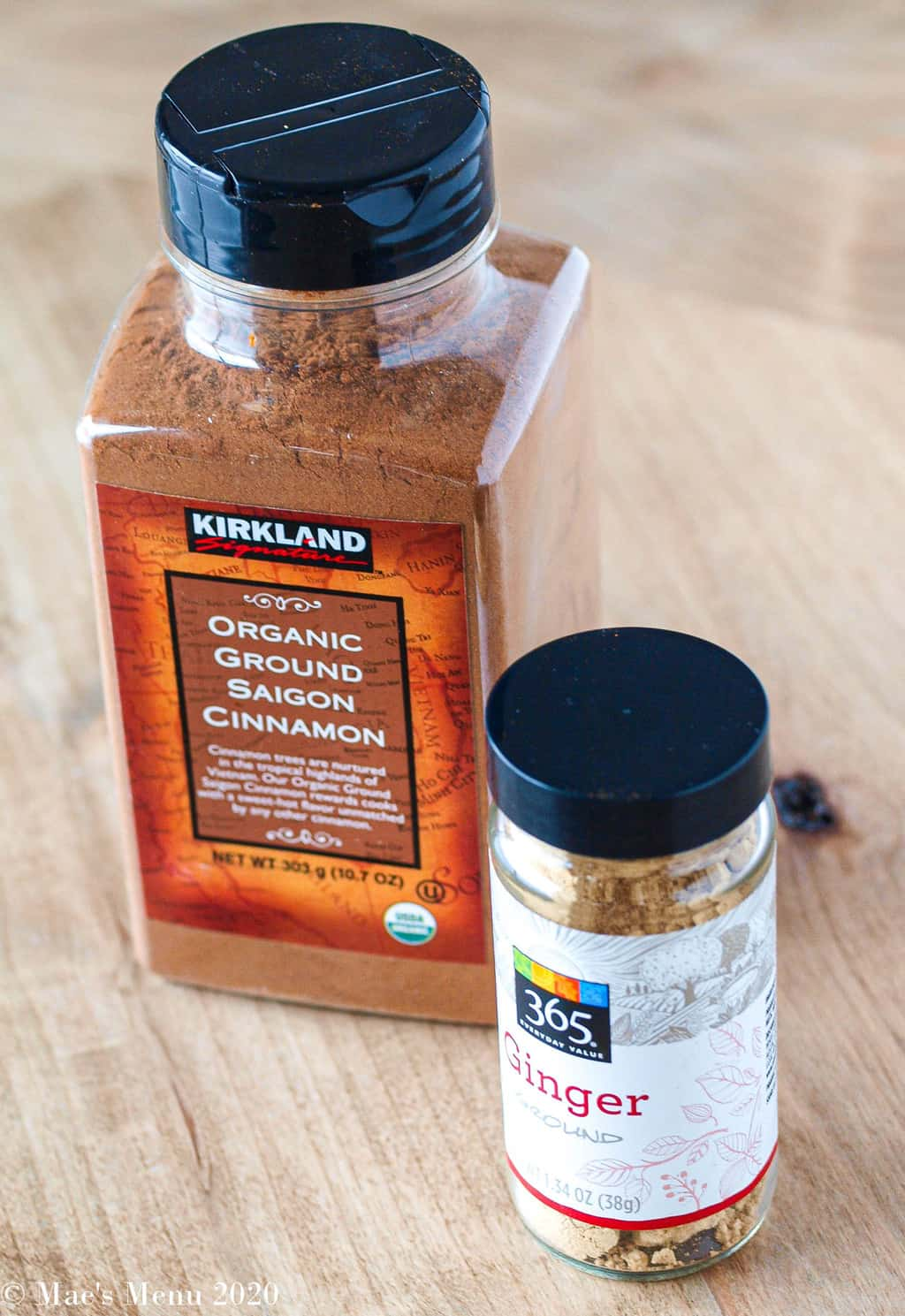 A large kirkland bottle of saigon cinnamon next to a small bottle of ginger powder