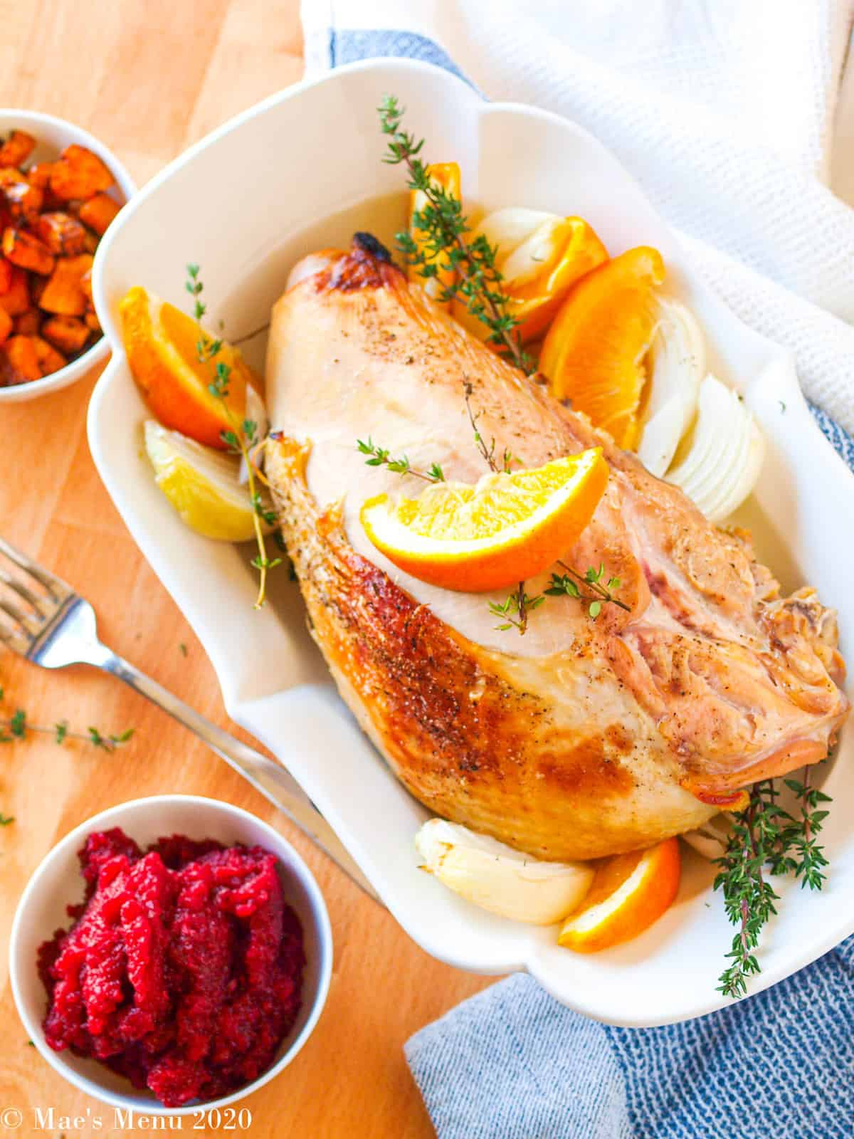 A roasted turkey breast next to a small dish of apple cranberry sauce