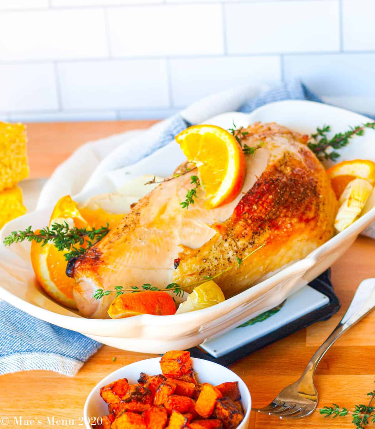 A side-angle shot of a roast turkey breast in a serving bowl