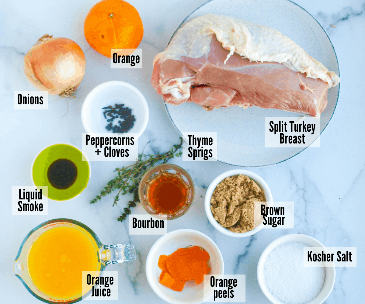 A shot of the ingredients in this best turkey breast brine: orange, onions, turkey breast, thyme sprigs, peppercorn, cloves, liquid smoke, bourbon, brown sugar, orange juice, orange peels, and kosher salt