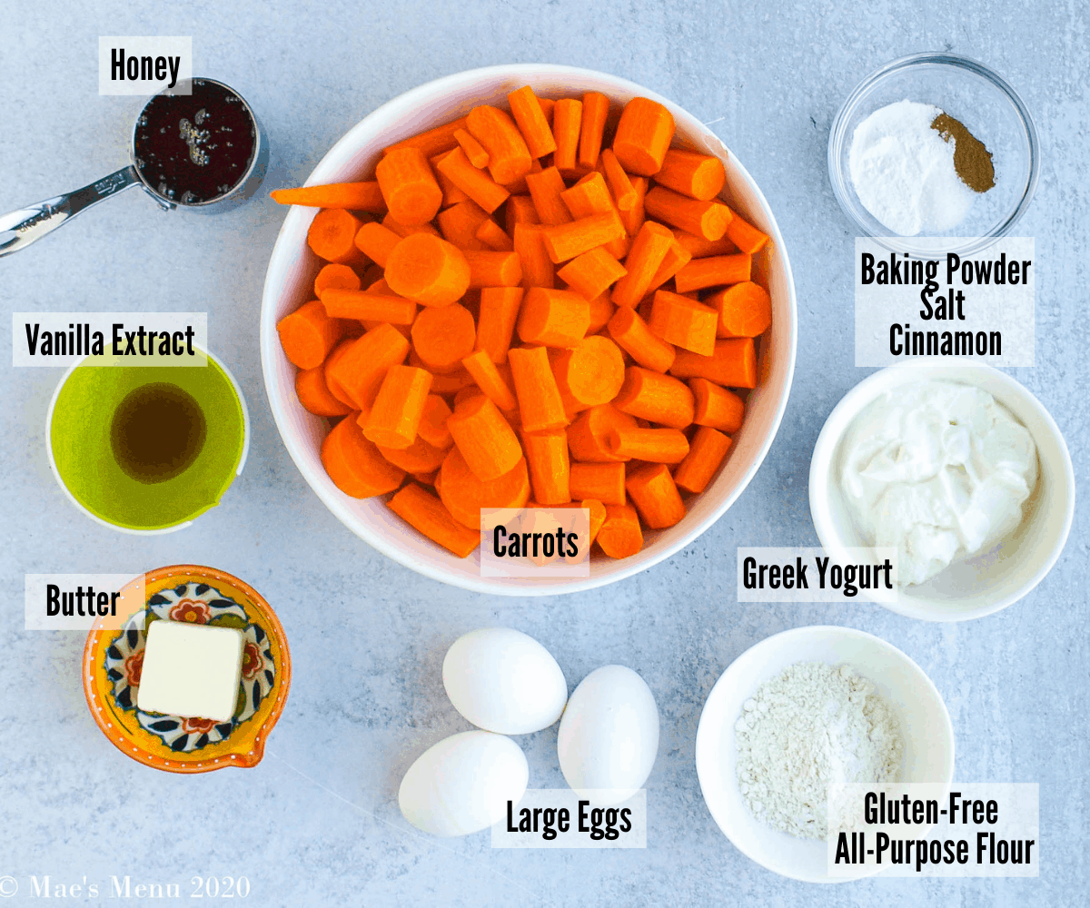 All of the ingredients for the carrot souffle recipe: honey, vanilla extract, butter, carrots, large eggs, all-purpose flour, Greek yogurt, baking powder, salt, and cinnamon