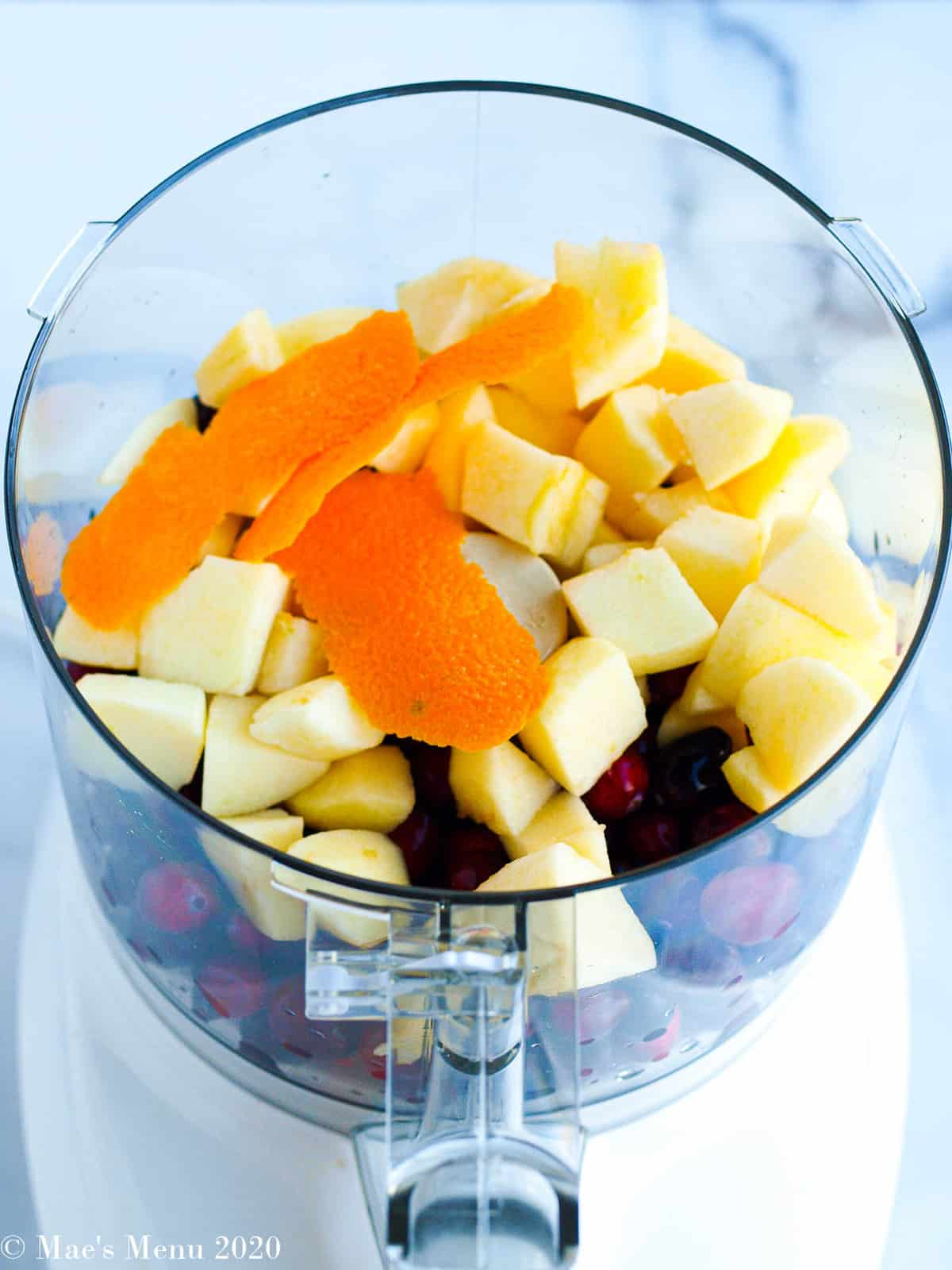 Orange peel, apple chunks, and fresh cranberries in a food processor
