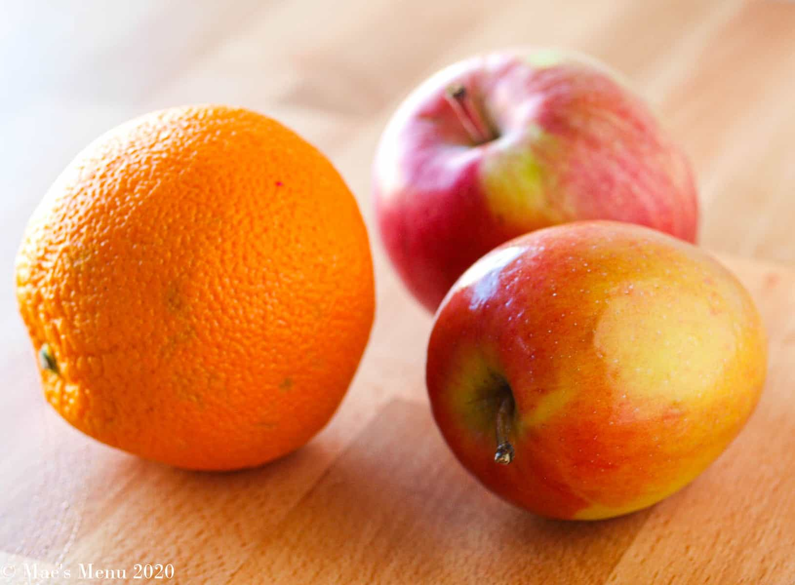 Two red apples and an orange on a butcher block counter