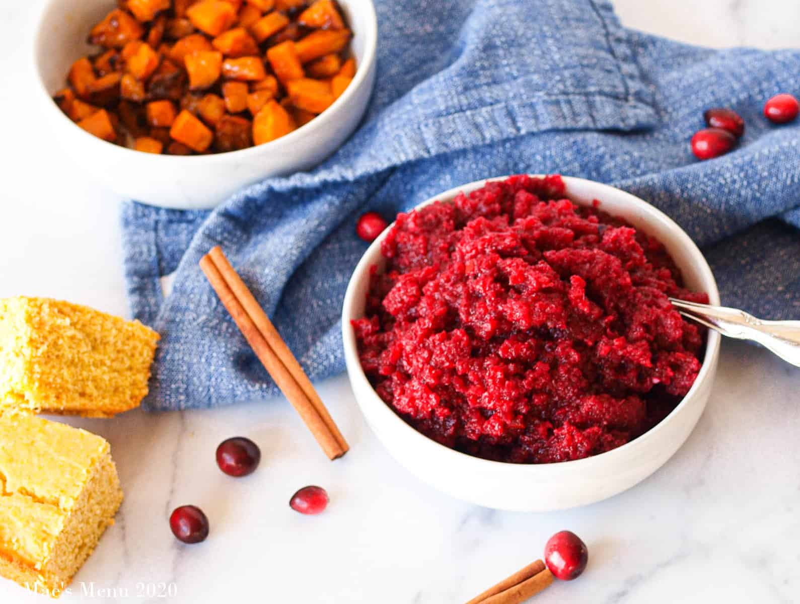 A bowl of apple cranberry sauce next to pieces of cornbread, a bowl of air fryer butternut squash, cinnamon sticks, and cranberries
