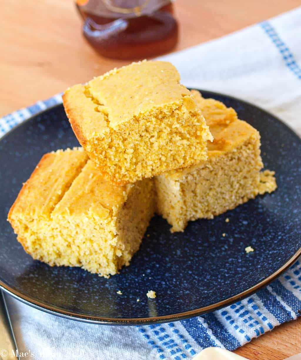 An angled overhead shot of gluten-free corn bread on a blue plate
