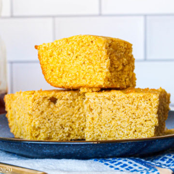 A Stack of gluten-free corn bread on a blue plate with white tile in the background