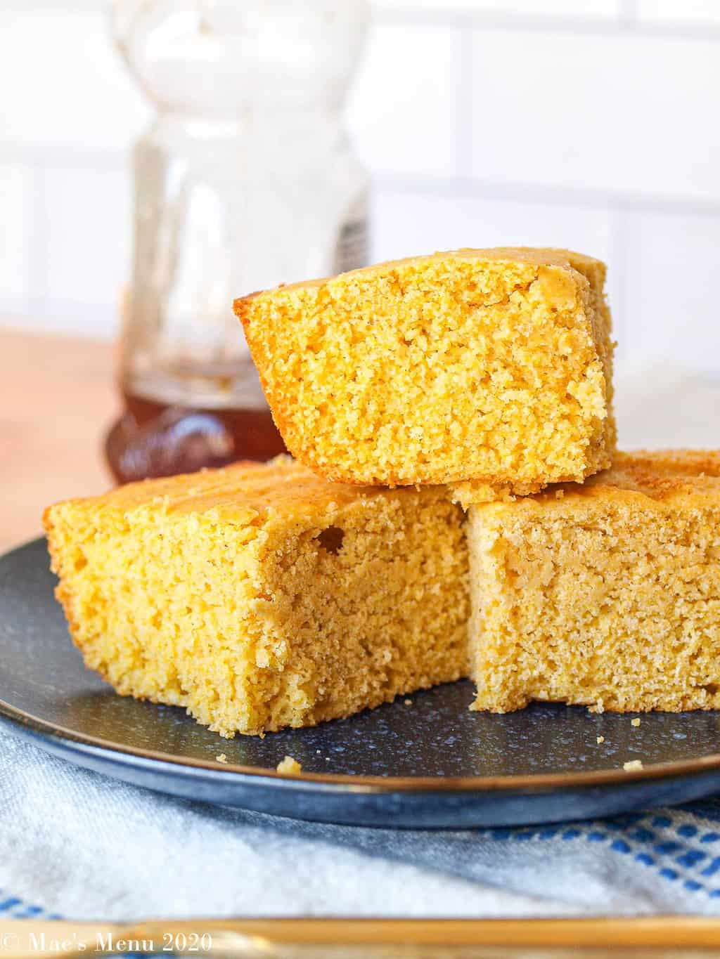 an up-close shot of 3 pieces of gluten-free cornbread on a blue plate