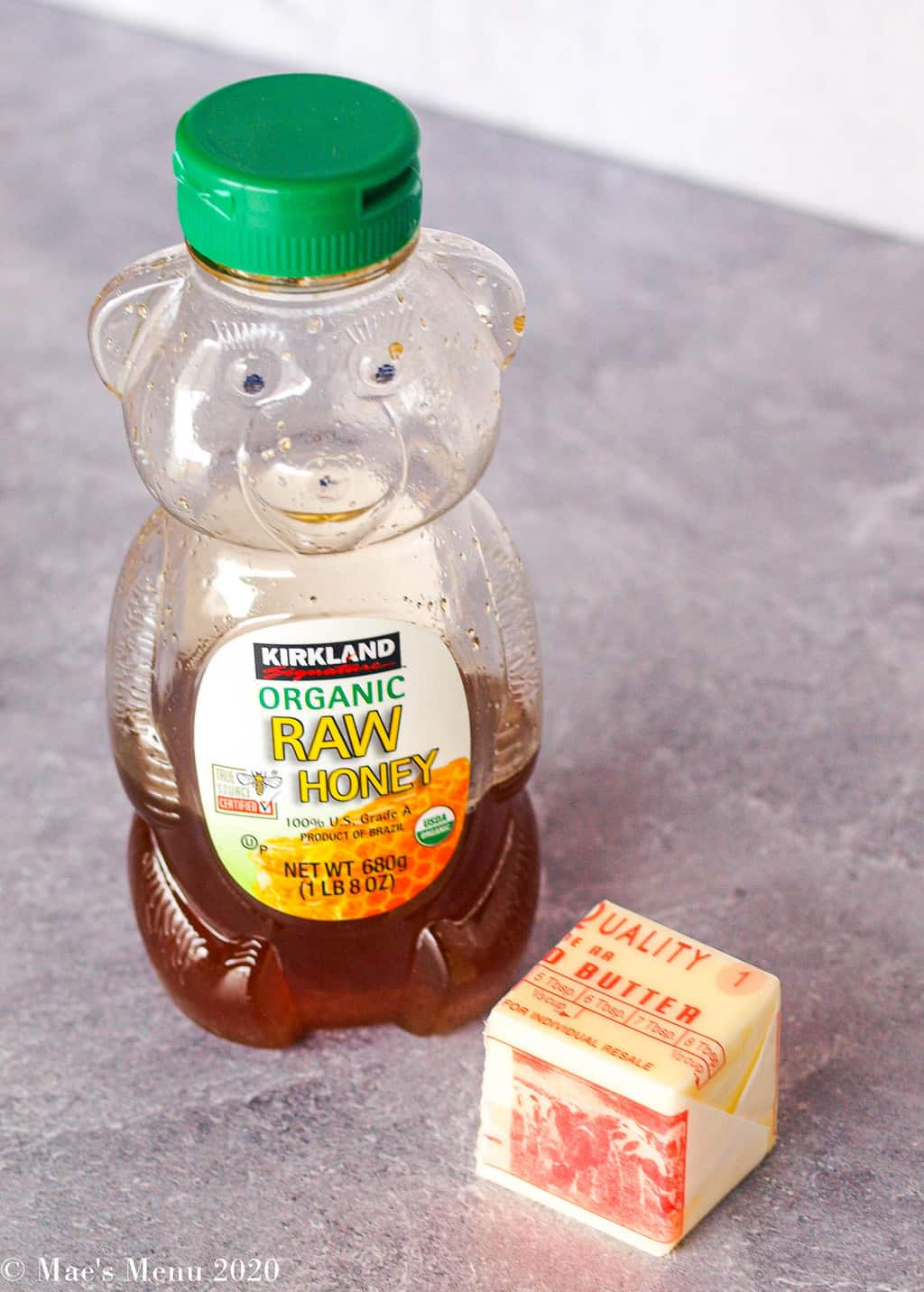 A honey bear of honey and a ¼ cup stick of butter on concrete