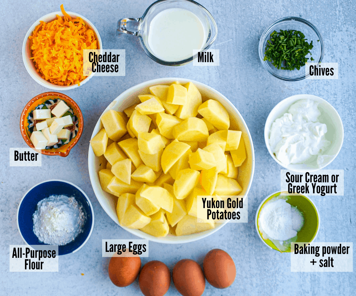 All the ingredients for twice-baked mashed potato souffle: Yukon gold potatoes, milk, cheddar cheese, butter, all-purpose flour, large eggs, baking powder & salt, sour cream or yogurt, and chives