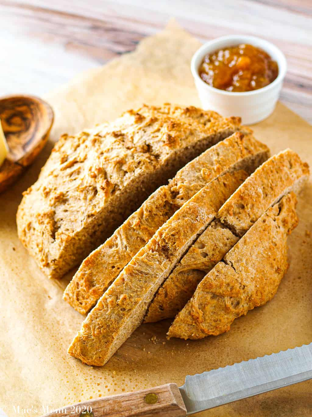 An angled shot of whole wheat beer bread, sliced on a sheet of parchment paper